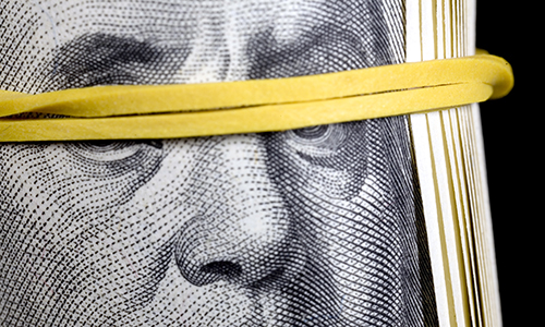 Ben Franklin image from hundred dollar bill with eyes covered by yellow elastic blindfold